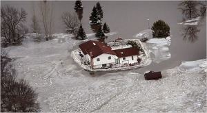 Ice and floodwaters surround a home near Fargo, ND