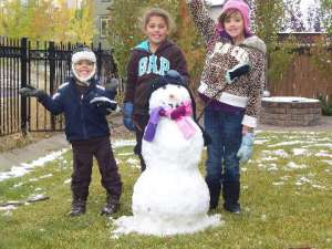 Children build a snowman in Calgary Oct.4.09