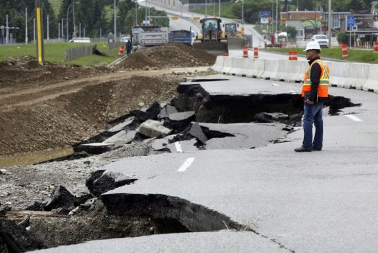 Worker surveys flooding damage to MacLeod Trail in Calgary, 24 June 2013 (CP)