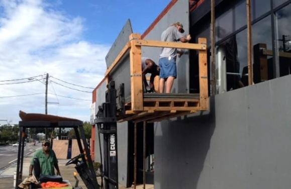 Workers board up a hardware store in Pensacola, Florida, USA (AP)