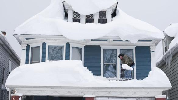 Man shovels snow off roof in Buffalo, NY, USA (Reuters)