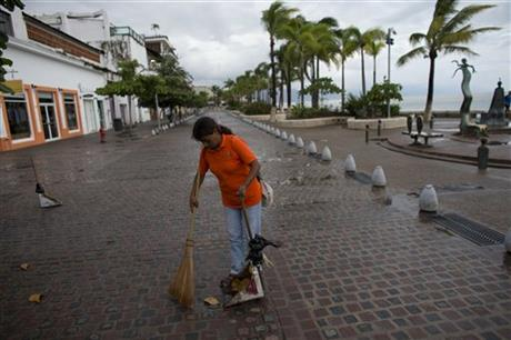 Woman sweeps debris in Puerto Vallarta, Mexico, 24 Oct 2015 (AP)